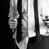 11961754 - image of a man holding a microphone and a drink dressed nicely